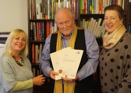 Dr. Janine Brooks MBE & Helen Caton-Hughes from the Dental Coaching Academy receive the PGC Level 7 certificates from Nigel Girling